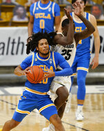 UCLA guard Tyger Campbell, left, fires the ball to the rim as Colorado guard McKinley Wright IV defends as time runs out in the first half of an NCAA college basketball game Saturday, Feb. 27, 2021, in Boulder, Colo. (AP Photo/David Zalubowski)