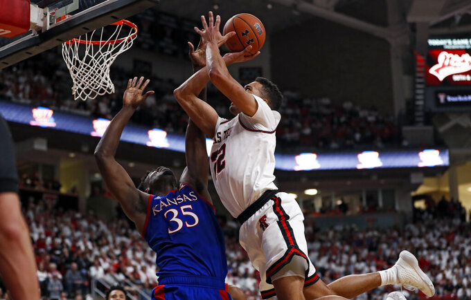 Texas Tech's TJ Holyfield (22) shoots the ball over Kansas' Udoka Azubuike (35) during the first half of an NCAA college basketball game Saturday, March 7, 2020, in Lubbock, Texas. (AP Photo/Brad Tollefson)