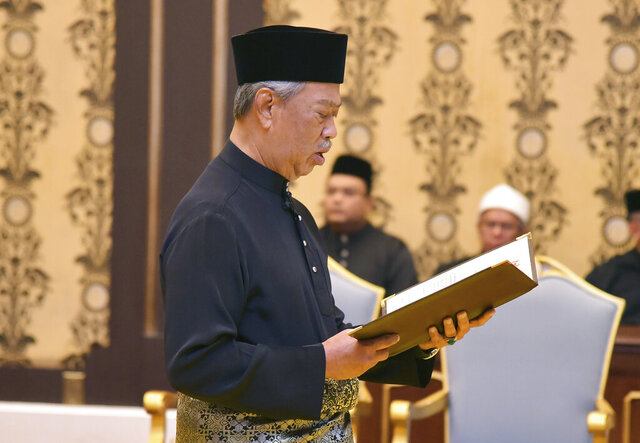 In this Malaysia's Department of Information photo taken and released on March 1, 2020, Malaysia's incoming Prime Minister Muhyiddin Yassin takes the oath of office in front of King Sultan Abdullah Sultan Ahmad Shah during his swearing-in ceremony as the country's new leader at the National Palace in Kuala Lumpur. (Maszuandi Adnan/Malaysia's Department of Information via AP)