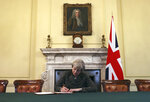 FILE - In this Tuesday March 28, 2017 file photo Britain's Prime Minister Theresa May, sitting below a painting of Britain's first Prime Minister Robert Walpole, signs the official letter to European Council President Donald Tusk, in 10 Downing Street, London, invoking Article 50 of the bloc's key treaty, the formal start of exit negotiations. Theresa May says she'll quit as UK Conservative leader on June 7, sparking contest for Britain's next prime minister. (Christopher Furlong/Pool Photo via AP, File)