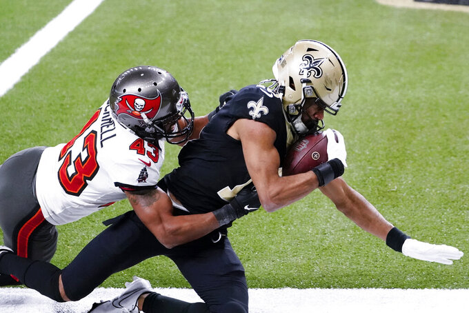 New Orleans Saints wide receiver Tre'Quan Smith, right, is hit by Tampa Bay Buccaneers defensive back Ross Cockrell (43) as Smith scores a touchdown during the second half of an NFL divisional round playoff football game, Sunday, Jan. 17, 2021, in New Orleans. (AP Photo/Brynn Anderson)
