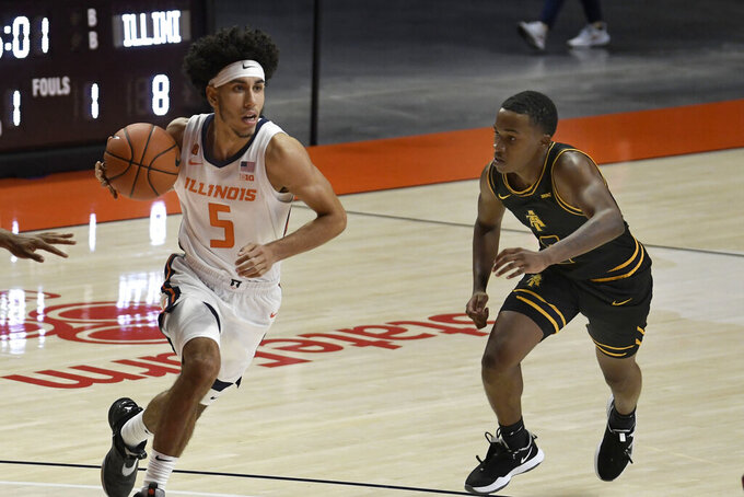 Illinois' Andre Curbelo (5) drives past North Carolina A&T's Fred Cleveland, Jr. (2) during the first half of an NCAA college basketball game, Wednesday, Nov. 25, 2020, in Champaign, Ill. (Photo/Holly Hart)