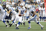 Indianapolis Colts quarterback Andrew Luck (12) hands off to running back Marlon Mack (25) during the first half of an NFL football preseason game against the Seattle Seahawks, Thursday, Aug. 9, 2018, in Seattle. (AP Photo/Elaine Thompson)