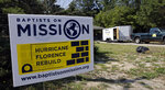 In this Tuesday, July 2, 2019, photo, signage is seen in the front yard of a Brinkley Street home as volunteers assist homeowners with ongoing repairs due to damage caused by Hurricane Florence the year before, in Spring Lake, N.C. North Carolina hurricane survivors are frustrated with the slow spending of federal long-term housing recovery funds. (AP Photo/Gerry Broome)