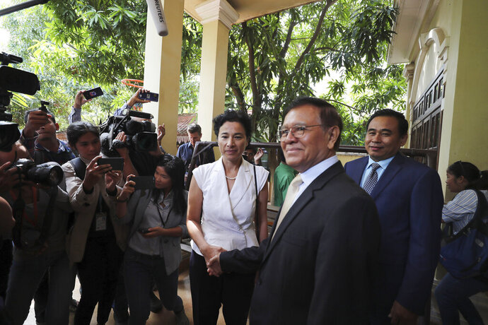 Cambodia National Rescue Party's President Kem Sokha, foreground, shakes hands with French Ambassador to Cambodia Eva Nguyen Binh, center, before a welcome meeting at his house in Phnom Penh, Cambodia, Monday, Nov. 11, 2019. A Cambodian court has lifted some restrictions on detained opposition leader Kem Sokha, essentially ending his house arrest. (AP Photo/Heng Sinith)