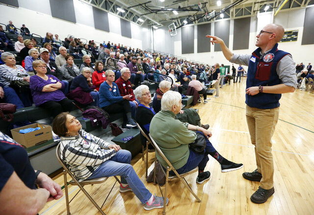 Christopher Le Mon, right, a precinct captain for former Vice President Joe Biden, counts supporters during the Democratic caucus at Hempstead High School in Dubuque, Iowa, on Monday, Feb. 3, 2020. (Nicki Kohl/Telegraph Herald via AP)