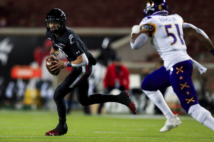 Cincinnati quarterback Desmond Ridder scrambles as he looks for a receiver during the second half of the team's NCAA college football game against East Carolina, Friday, Nov. 13, 2020, in Cincinnati. Cincinnati won 55-17. (AP Photo/Aaron Doster)