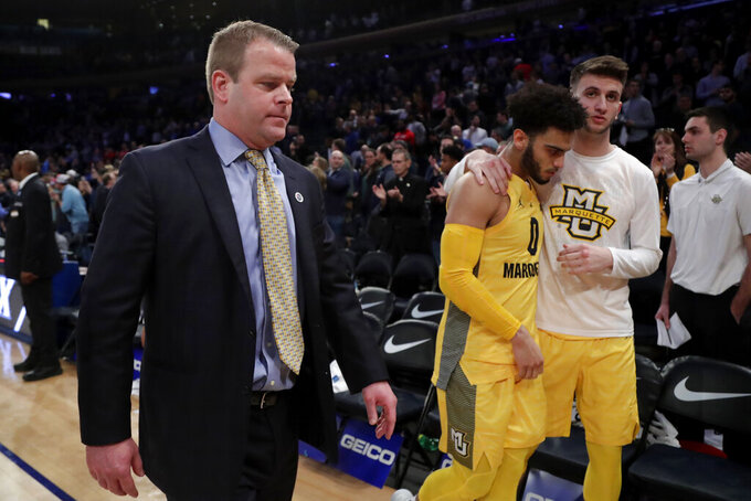 Marquette head coach Steve Wojciechowski, left, guard Markus Howard, center, and guard Buddy Jaffee leave the court after losing to Seton Hall in an NCAA college basketball semifinal game in the Big East men's tournament, early Saturday, March 16, 2019, in New York. Seton Hall won 81-79. (AP Photo/Julio Cortez)