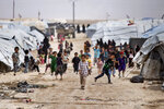 Children gather outside their tents, at al-Hol camp, which houses families of members of the Islamic State group, in Hasakeh province, Syria, Saturday, May 1, 2021.  It has been more than two years that some 27,000 children have been left to languish in al-Hol camp, which houses families of IS members.   Most of them not yet teenagers, they are spending their childhood in a limbo of miserable conditions with no schools, no place to play or develop and seemingly no international interest in resolving their situation.   (AP Photo/Baderkhan Ahmad)