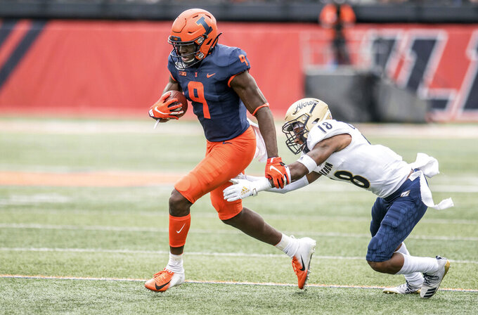 Illinois wide receiver Josh Imaforbhebhe (9) runs from the grasp of Akron's Randy Cochran Jr. (18) in the first half of an NCAA college football game between Illinois and Akron, Saturday, Aug. 31, 2019, in Champaign, Ill. (AP Photo/Holly Hart)