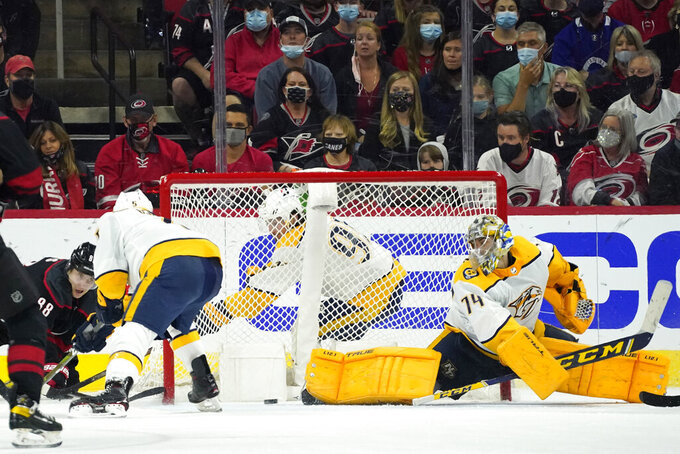 Carolina Hurricanes center Martin Necas, left, shoots and scores against Nashville Predators goaltender Juuse Saros (74) during the third period in Game 5 of an NHL hockey Stanley Cup first-round playoff series in Raleigh, N.C., Tuesday, May 25, 2021. (AP Photo/Gerry Broome)