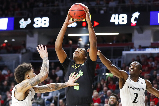 South Florida's Michael Durr, center, shoots against Cincinnati's Jarron Cumberland, left, and Keith Williams (2) in the second half of an NCAA college basketball game, Tuesday, Jan. 15, 2019, in Cincinnati. (AP Photo/John Minchillo)