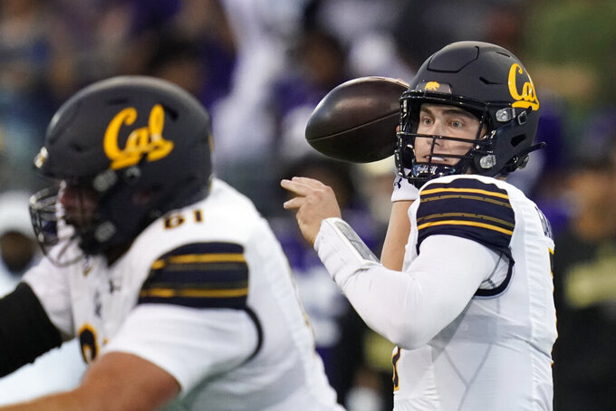 California quarterback Chase Garbers, right, passes against Washington during the first half of an NCAA college football game, Saturday, Sept. 25, 2021, in Seattle. (AP Photo/Elaine Thompson)