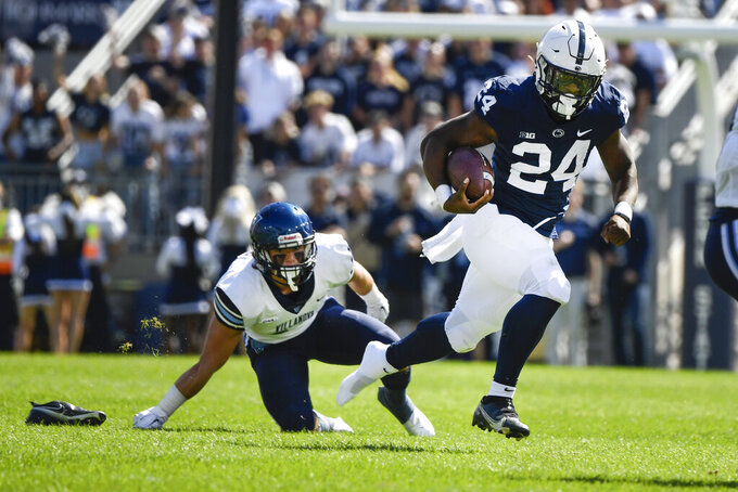 Penn State running back Keyvone Lee (24) runs out of his shoe as Villanova defensive back Ethan Potter (34) looks on during the second quarter of an NCAA college football game in State College, Pa., on Saturday, Sept.25, 2021. (AP Photo/Barry Reeger)