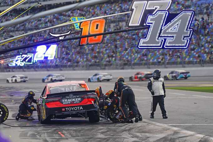 Martin Truex Jr.'s crew repairs damage to his car during a pit stop in the NASCAR Cup Series road course auto race at Daytona International Speedway, Sunday, Feb. 21, 2021, in Daytona Beach, Fla. (AP Photo/John Raoux)