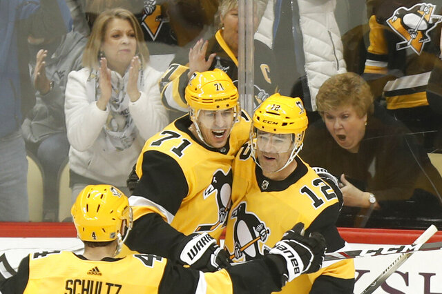 Fans celebrate behind Pittsburgh Penguins' Evgeni Malkin (71) and Justin Schultz (4) as they greet Patrick Marleau (12) who scored against the Carolina Hurricanes during the first period of an NHL hockey game, Sunday, March 8, 2020, in Pittsburgh. (AP Photo/Keith Srakocic)