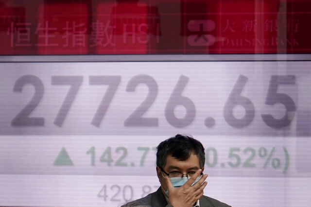 A man walks past an electronic board showing Hong Kong share index outside a local bank in Hong Kong, Wednesday, Feb. 12, 2020. Asian shares were higher Wednesday, although the outbreak of a new virus in the region continued to weigh on investor sentiments. (AP Photo/Kin Cheung)