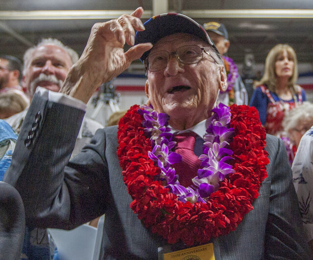 FILE - In this Dec. 7, 2016, file photo, Donald Stratton, center, a USS Arizona survivor, acknowledges a friend at Kilo Pier next to the World War II Valor in the Pacific National Monument at Joint Base Pearl Harbor-Hickam in Honolulu. Stratton passed away in his sleep at his Colorado Springs home Saturday, Feb. 16, 2020 with his family in attendance. Stratton was one of the survivors of the Dec. 7, 1941, Japanese aerial attack on the U.S. Navy base at Pearl Harbor in Hawaii that killed 1,100 Arizona crew members. (AP Photo/Eugene Tanner, File)