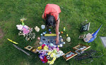 Melany Zoumadakis arranges photos and flowers that she brought to the grave of her daughter, Tanna Jo Fillmore, on April 26, 2019, in Salt Lake City. Fillmore killed herself in 2016 while being held on a probation violation. She had threatened to harm herself after she told her mother she was being denied her prescription medicines. Her mother has filed suit. (AP Photo/Rick Bowmer)