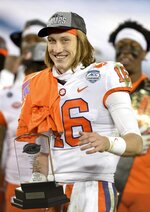Clemson quarterback Trevor Lawrence holds the MVP Trophy after defeating Notre Dame in the Atlantic Coast Conference championship NCAA college football game, Saturday, Dec. 19, 2020, in Charlotte, N.C. (Jeff Siner/The News & Observer via AP)