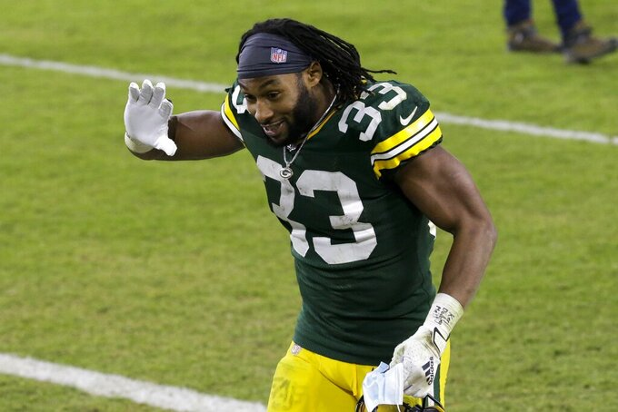 Green Bay Packers' Aaron Jones waves as he runs off the field after an NFL football game against the Carolina Panthers Saturday, Dec. 19, 2020, in Green Bay, Wis. The Packers won 24-16. (AP Photo/Mike Roemer)