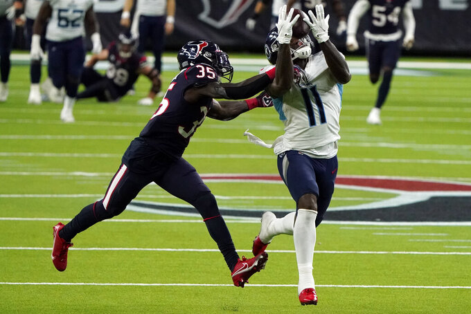 Tennessee Titans wide receiver A.J. Brown (11) makes a 52-yard pass reception as Houston Texans cornerback Keion Crossen (35) defends during the second half of an NFL football game Sunday, Jan. 3, 2021, in Houston. The Titans won 41-38. (AP Photo/Eric Christian Smith)