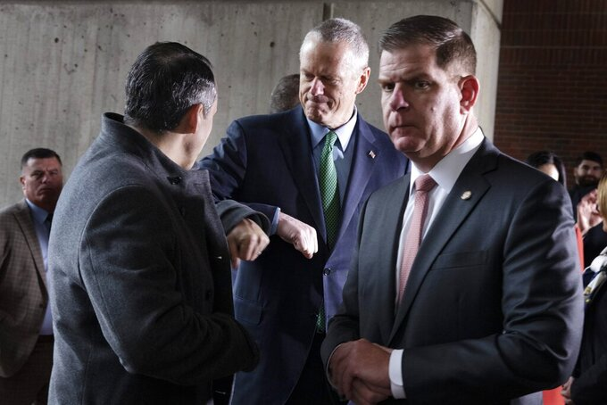 Massachusetts Gov. Charlie Baker, center, bumps elbows with state Rep. Aaron Michlewitz, left, behind Boston Mayor Marty Walsh, right, following a news conference announcing the postponement of the Boston Marathon, Friday, March, 13, 2020, in Boston. The Marathon, which was due to be run on April 20,  will be run on Monday, Sept. 14, 2020, due to concerns about the coronavirus. For most people, the new coronavirus causes only mild or moderate symptoms, such as fever and cough. For some, especially older adults and people with existing health problems, it can cause more severe illness, including pneumonia. The vast majority of people recover from the new virus. (AP Photo/Michael Dwyer)