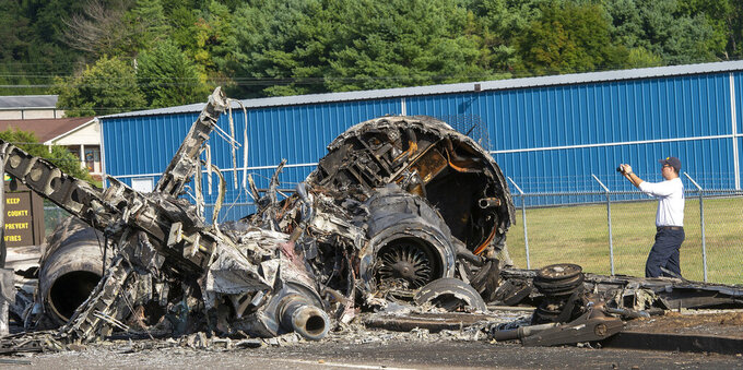 FILE - In this Aug. 16, 2019, file photo, a member of the National Transportation Safety Board looks at the wreckage of a plane that Dale Earnhardt Jr., his wife and daughter and two pilots and a dog were on when it crash landed at the Elizabethton Municipal Airport in Elizabethton, Tenn. Earnhardt Jr. and a pilot struggled to open a crashed airplane's rear exit door as the aircraft began to burn and fill with smoke before the race car driver and his family managed to escape from the main door, according to new details about the 2019 accident released by the National Transportation and Safety Board.(David Crigger/Bristol Herald Courier via AP, File)
