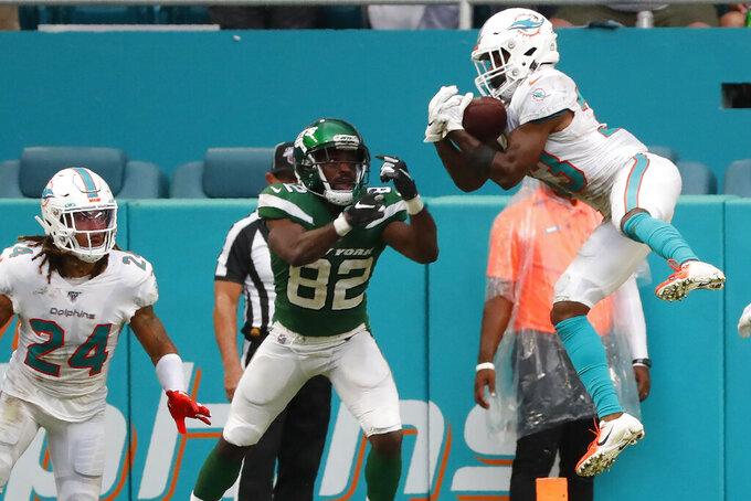 Miami Dolphins cornerback Jomal Wiltz (33) intercepts the ball against New York Jets wide receiver Jamison Crowder (82) during the first half of an NFL football game, Sunday, Nov. 3, 2019, in Miami Gardens, Fla. (AP Photo/Wilfredo Lee)