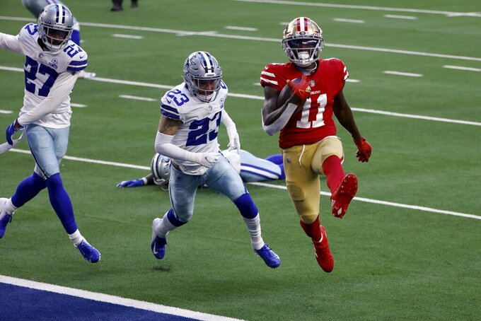 San Francisco 49ers wide receiver Brandon Aiyuk (11) high steps into the end zone after catching a pass for a touchdown in front of Dallas Cowboys' Trevon Diggs (27) and Darian Thompson (23) in the first half of an NFL football game in Arlington, Texas, Sunday, Dec. 20, 2020. (AP Photo/Ron Jenkins)