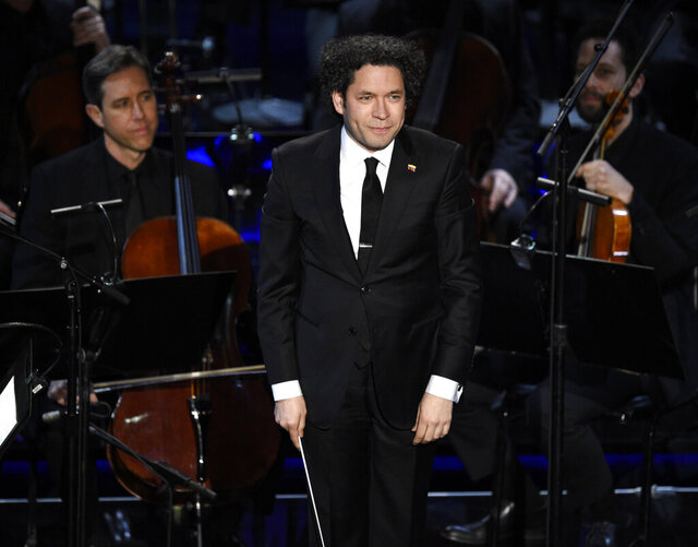 FILE - In this Feb. 24, 2019, file photo, conductor Gustavo Dudamel reacts to the audience after conducting the LA Philharmonic performance during the 'In Memoriam' at the Oscars at the Dolby Theatre in Los Angeles. Dudamel will remain as music and artistic director of the Los Angeles Philharmonic for five more years. The 38-year-old Venezuelan conductor made his debut with the LA Philharmonic in 2005 and was named director in 2009. (Photo by Chris Pizzello/Invision/AP via AP, File)