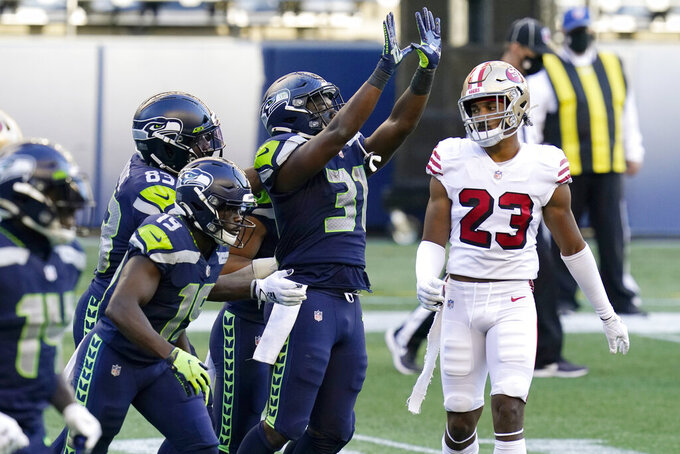 Seattle Seahawks running back DeeJay Dallas (31) celebrates in front of San Francisco 49ers cornerback Ahkello Witherspoon (23) after Dallas scored a touchdown during the second half of an NFL football game, Sunday, Nov. 1, 2020, in Seattle. (AP Photo/Elaine Thompson)
