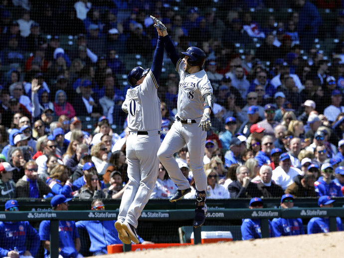Milwaukee Brewers' Ryan Braun, right, celebrates with third base coach Ed Sedar after hitting a solo home run against the Chicago Cubs during the fourth inning of a baseball game Friday, May 10, 2019, in Chicago. (AP Photo/Nam Y. Huh)