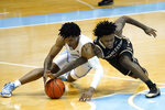 North Carolina guard Caleb Love, left, and College of Charleston guard Zep Jasper chase a loose ball during the first half of an NCAA basketball game in Chapel Hill, N.C., Wednesday, Nov. 25, 2020. (AP Photo/Gerry Broome)