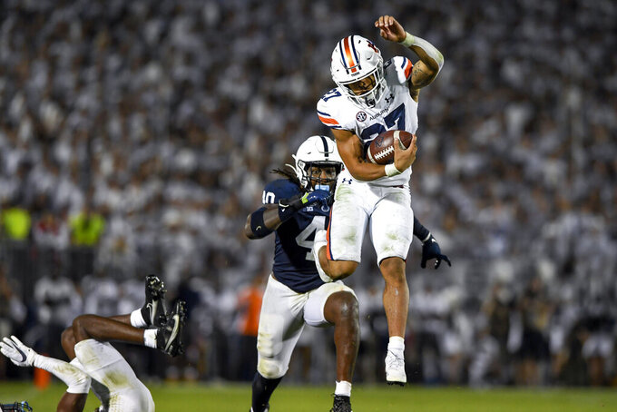 Auburn running back Jarquez Hunter (27) leaps as Penn State linebacker Jesse Luketa (40) pursues him in the fourth quarter of an NCAA college football game in State College, Pa., Saturday, Sept. 18, 2021. (AP Photo/Barry Reeger)