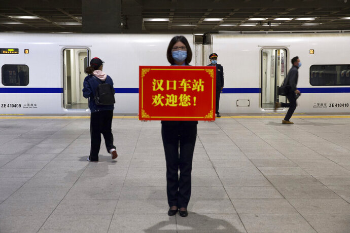 A railway worker holds a sign reading