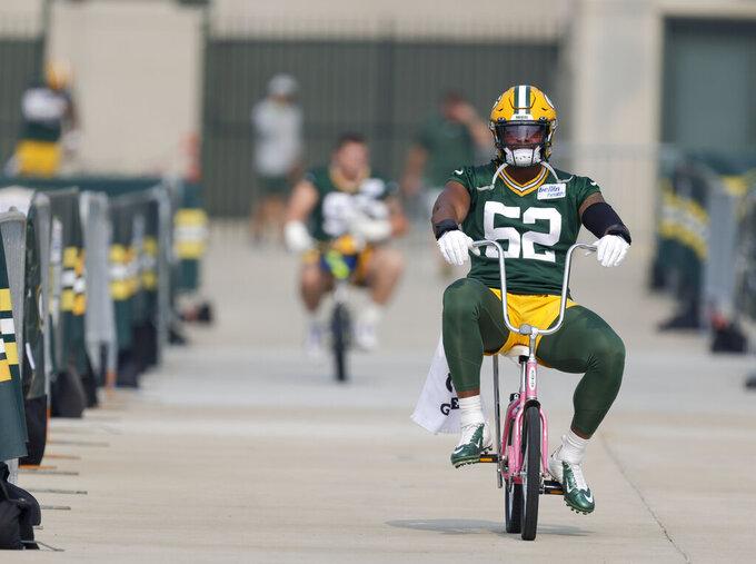 Green Bay Packers' linebacker Rashan Gary rides a bicycle to NFL football training camp Saturday, July 31, 2021, in Green Bay, Wis. (AP Photo/Matt Ludtke)