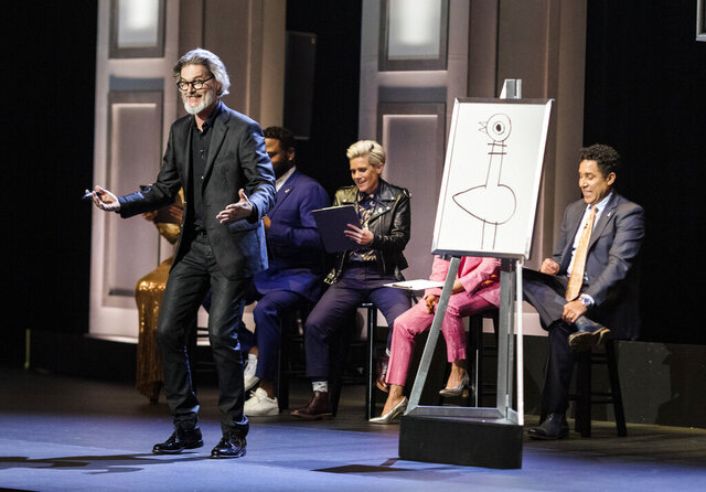 """This image released by HBO Max shows author and illustrator Mo Willems, standing, in """"Don't Let the Pigeon Do Storytime!"""" The special was filmed last year at the Kennedy Center and features comedy inspired by Willems' books for children. (HBO Max via AP)"""