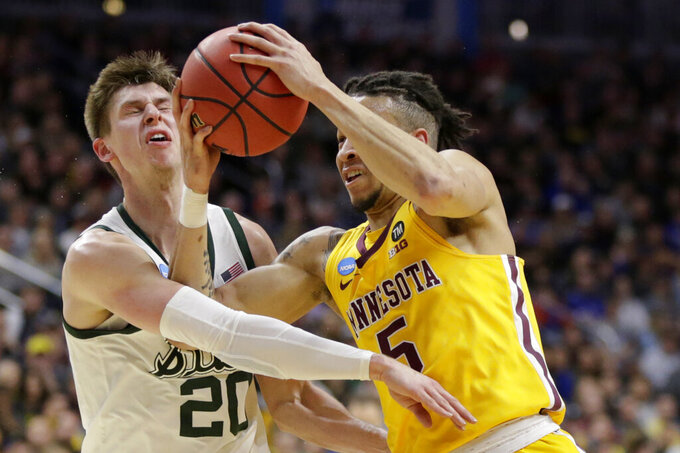 Minnesota's Amir Coffey (5) tries to get past Michigan State's Matt McQuaid (20) during the first half of a second round men's college basketball game in the NCAA Tournament, in Des Moines, Iowa, Saturday, March 23, 2019. (AP Photo/Nati Harnik)