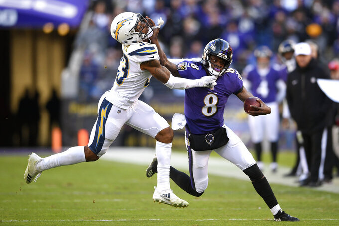 Baltimore Ravens quarterback Lamar Jackson, right, rushes against Los Angeles Chargers free safety Derwin James in the second half of an NFL wild card playoff football game, Sunday, Jan. 6, 2019, in Baltimore. (AP Photo/Nick Wass)