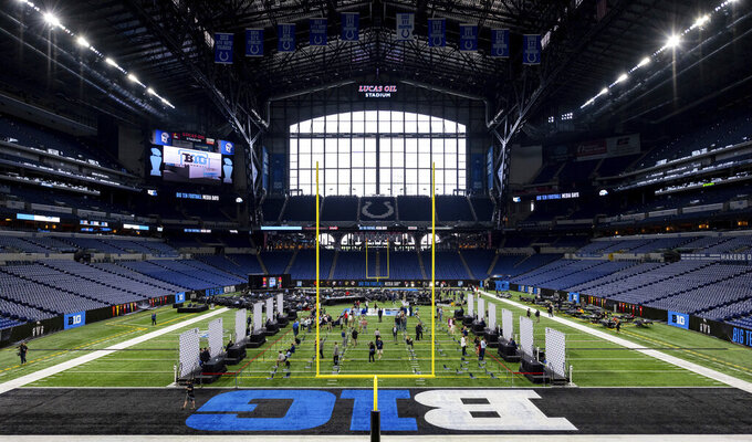 NCAA college football players and coaches take turns at a podiums to respond to reporter's questions at the Big Ten Conference media days, Thursday, July 22, 2021, at Lucas Oil Stadium in Indianapolis. (AP Photo/Doug McSchooler)