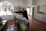 In this Sunday, Oct. 20, 2019 photo, Rev. William Tourigny, 66, pastor of St. Rose de Lima Parish, in Chicopee, Mass., arranges vestments while preparing to offer Mass at the Catholic church. When Tourigny was ordained in 1980, the Springfield diocese had more than 300 priests serving 136 parishes. Since then, the ranks of priests have shrunk by more than half and nearly 60 of the parishes have closed. For Tourigny, it's meant many more funerals to handle, including dozens related to drug overdoses and heavy drinking. (AP Photo/Steven Senne)