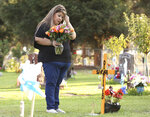 Lori Gonzalez wipes a tear away after visiting the temporary grave marker of her sister and Kaiser Permanente Fresno Medical Center nurse, Sandra Oldfield, at the Sanger Cemetery in Sanger, Calif., Saturday, Aug. 29, 2020. Oldfield died after being exposed to the novel coronavirus. Workers at the hospital said they did not have the proper personal protective equipment. (AP Photo/Gary Kazanjian)