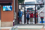 Philadelphia Phillies' fans watch from the gate outside of the stadium just past center field during the first inning of a baseball game against the Miami Marlins, Friday, July 24, 2020, in Philadelphia. (AP Photo/Chris Szagola)