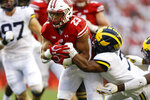 Wisconsin running back Jonathan Taylor, left, runs against Michigan's Khaleke Hudson, right, during the first half of an NCAA college football game Saturday, Sept. 21, 2019, in Madison, Wis. (AP Photo/Andy Manis)