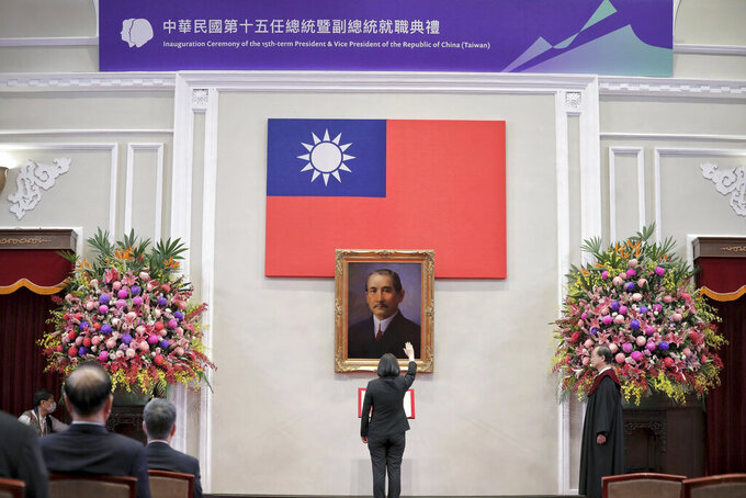 In this photo released by the Taiwan Presidential Office, Taiwanese President Tsai Ing-wen raises her hand during an inauguration ceremony before a portrait of Sun Yat-sen at the Presidential office in Taipei, Taiwan on Wednesday, May 20, 2020. Tsai was inaugurated for a second term amid increasing pressure from China on the self-governing island democracy it claims as its own territory. (Taiwan Presidential Office via AP)