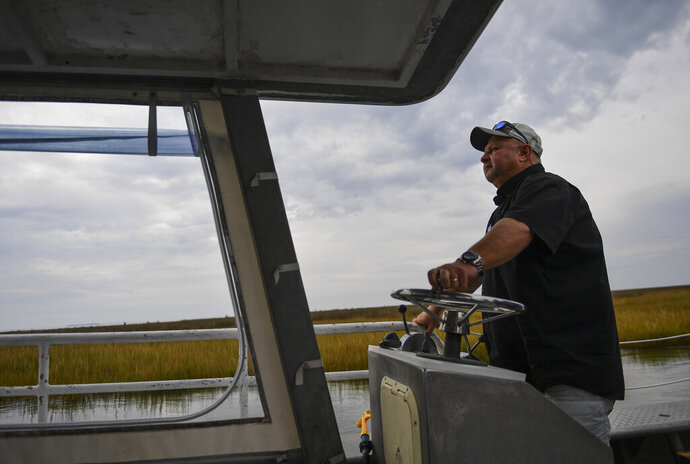 In this Oct. 30, 2019 photo, Larry Laird pilots a boat with media members for a tour in Fox Island, Va. Chesapeake Bay Foundation's Fox Island Environmental Education Program will be closing for good due to rising sea levels and erosion of the protective marshes surrounding the center. The Lodge, which was originally a hunting and fishing lodge in the Chesapeake Bay, just over into the Virginia side, housed its last group of school kids a few days ago. (Ricky Carioti/The Washington Post via AP)