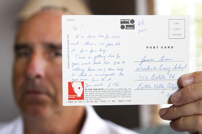 James Grein, 61, at his house in Sterling, Va., Friday, July 26, 2019, holds a Florida postcard sent to him when he was 15 years old by now-defrocked Cardinal Theodore McCarrick. Letters and postcards from McCarrick wrote to three men he allegedly sexually abused and harassed show how he groomed his victims, experts say. (AP Photo/Manuel Balce Ceneta)