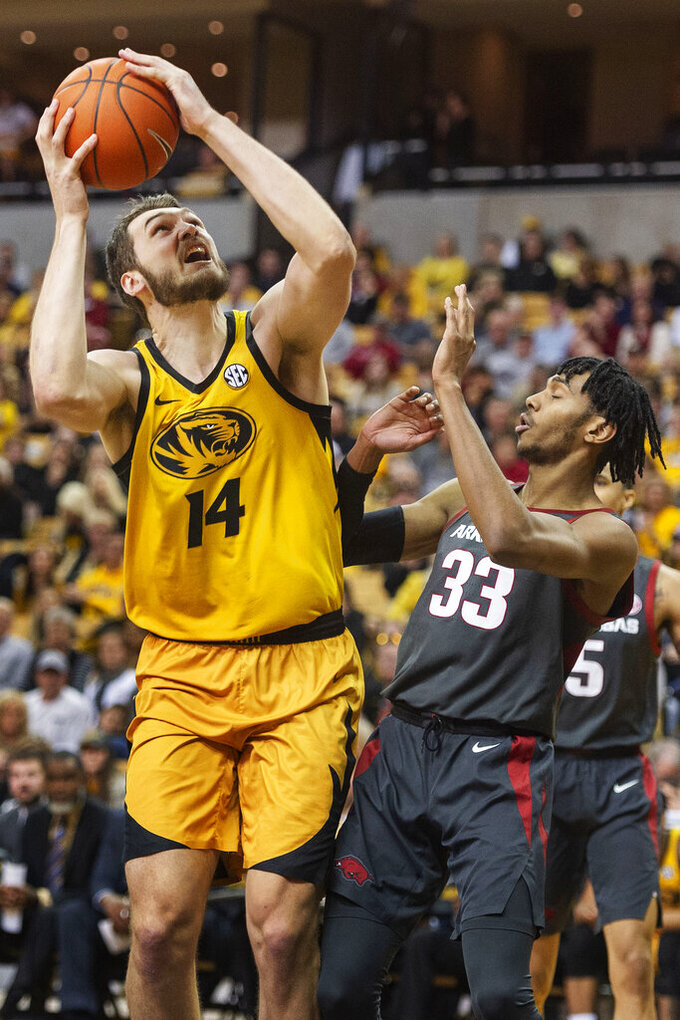 Missouri's Reed Nikko, left, shoots over Arkansas' Jimmy Whitt Jr., right, during the second half of an NCAA college basketball game Saturday, Feb. 8, 2020, in Columbia, Mo. Missouri beat Arkansas 83-79 in overtime. (AP Photo/L.G. Patterson)