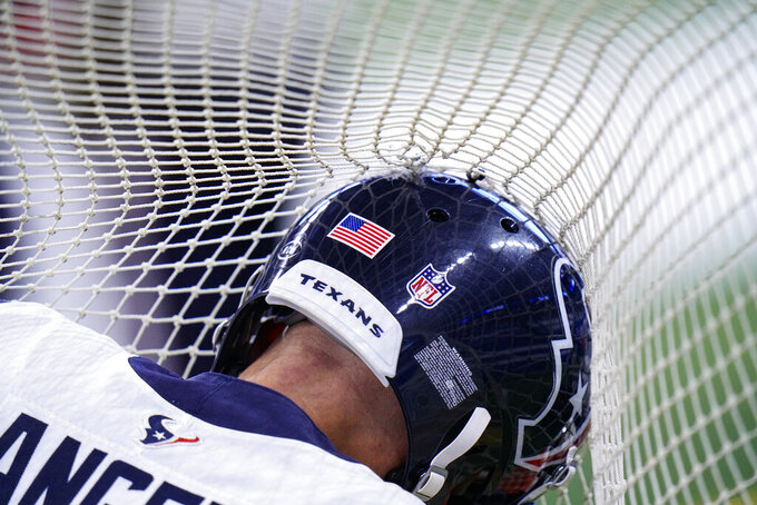 Houston Texans punter Bryan Anger (9) reaches into the net for a football as he warms up on the sideline in the first half of an NFL football game against the Indianapolis Colts in Indianapolis, Sunday, Dec. 20, 2020. (AP Photo/AJ Mast)